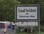 Ortsschild von Saalfelden mit Auto