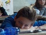 Müder Schüler liegt auf der Schulbank