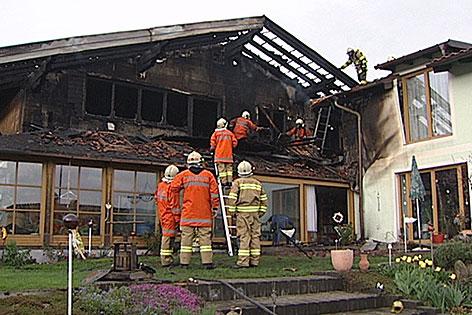 Ausgebranntes Wohnhaus in Thalgau mit Feuerwehrleuten
