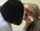 Ärztin untersucht Ohr eines Patienten
