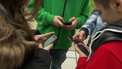 Jugendliche mit Handys stehen im Kreis