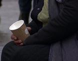 Bettlerin mit Becher sitzt in der Fußgängerzone