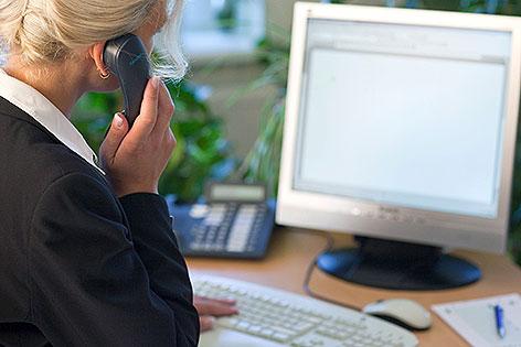 Frau sitzt vor Computer und telefoniert