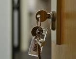 Ein Schlüssel im Schlüsselloch öffnet eine Wohnung