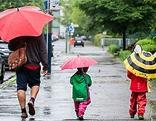 Mann mit Kindern und Regenschirmen