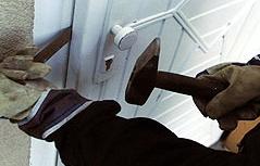 Einbrecher beim Aufbrechen einer Wohnungstür (gestellte Szene)