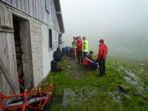 Rettungskräfte vor der Alm bei schlechtem Wetter