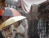 Bei regnerischem Wetter spazieren zwei Frauen mit Regenschirm