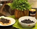 Heidelbeeren in der Schüssel, Heidelbeermarmeladebrot, Heidelbeermarmelade im Glas und ein Strauß Farn und Blätter in einer Vase