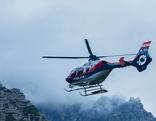 Polizeihubschrauber fliegt im Gebirge