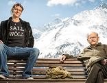 2 Künstler sitzen auf Holzbank, dahinter die Alpen