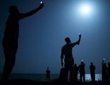Migranten in Dschibuti strecken ihre Handys in die Luft für besseres Signal