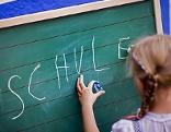 Mädchen in Schulklasse vor Schultafel