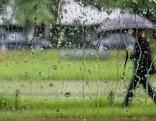Mensch spaziert mit Regenschirm, durch eine verregnete Glasscheibe fotografiert