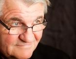 Peter Turrini ist seitlich von oben zu sehen in schwarzem Hemd mit schwarzem Hintergrund