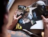 Sharukh sucht Fotos aus, Blick von oben auf die Fotos in seinem Schoß