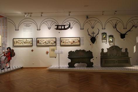 Ausstellung im Hofmobiliendepot, zwei Bänke im Vordergrund, dahinter Bilder aus dem Klebealbum
