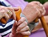 Seniorenhände mit Stöcken