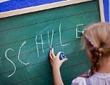 """Kind schreibt """"Schule"""" auf Tafel"""
