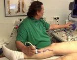 Arzt beim Ultraschall einer Beinader