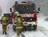 Feuerwehrleute und Feuerwehrauto im Einsatz im Schnee