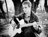 Mann mit Gitarre im Wald