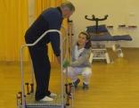 Therapeutin mit Patienten am Gleichgewichtstrainer