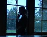 Frau am Fenster im Schatten