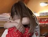 Gewalt gegen Kinder, Mädchen sitzt verzweifelt neben Bett