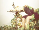 Frau schläft am Tisch von Blättern umhüllt