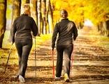 Zwei Frauen mit Walking-Stöcken im Herbstwald