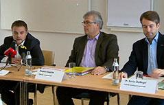 Metallergewerkschafter sitzen am Tisch bei Pressekonferenz