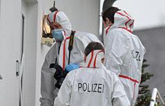 Polizisten in weißen Überzügen bei Hauseingang
