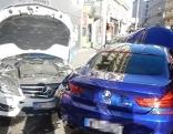 Zwei beschädigte Pkws mit geöffneter Motorhaube
