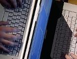 Hände tippen auf Laptops