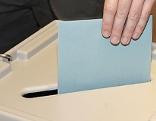 Mann wirft Kuvert in eine Wahlurne