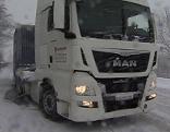 Lkw auf Schneefahrbahn mit Schneeketten