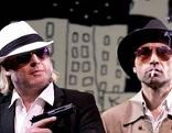Gregor Seberg hält eine Waffe in der Hand, neben ihm Gerald Votava mit einer Zigarette im Mund und einer Gitarre in der Hand