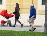Junge Frau mit Kinderwagen geht neben einem Pensionist