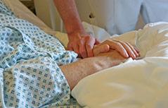 Pfleger hält Hand einer Patientin