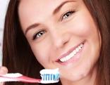 Frau mit Zahnbürste lächelnd