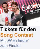 Patrick Budgen und Ulrike Dobes posieren vor Song-Contest-Logo