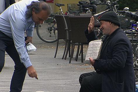 Passant gibt Bettler eine Münze