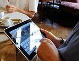 Gäste mit Zeitung und Tablet in Kaffeehaus