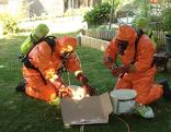Einsatzkräfte in Schutzuniform bei einem Chemieunfall