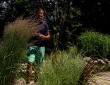 Karl Ploberger inmitten der Gräserstauden beim Teich im Fernsehgarten.
