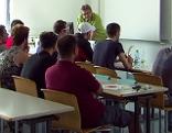 Flüchtlinge in einem Klassenraum beim Unterricht