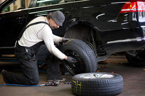 Servicetechniker wechselt Winterreifen am Auto