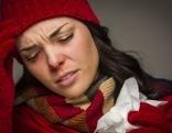 Frau mit roter Mütze, Schal und Handschuhe schaut schmerzerfüllt, hat ein Taschentuch in der Hand