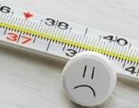 Fieberthermometer, im Vordergrund ein weiße, runde Tablette mit einem aufgezeichneten Gesicht, schaut traurig
